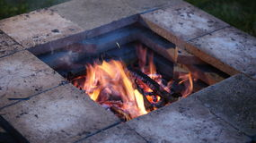 Fire Pit with burning fire. Evening close up of a stone fire pit with a burning fire inside of it Stock Photos