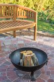 Fire bowl in the garden as a cozy place of rest with wooden bench in the background royalty free stock photography