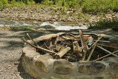 Fire Pit near River filled with Wood. Fire pit with scrap lumber and wood outdoors near a river Stock Images