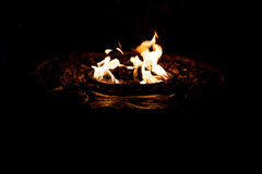 Fire pit. Scene of bright golden orange flame burning in a fire pit at night with dark surrounding Stock Photo