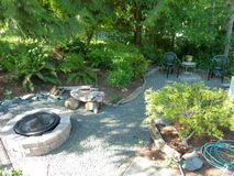 Fire pit and sitting area in back yard. Fire pit made of stone blocks and metal fire pit with driftwood chair and small sitting area with metal side table and Stock Photos