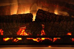 Fire-place with a fire and logs. A fire and logs is in a fire-place stock images