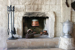 Fire-place in old house. Vintage fire-place with kitchen tools in old house stock photo