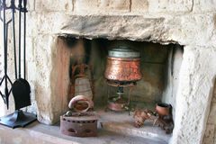 Fire-place in old house. Vintage fire-place with kitchen tools in old house royalty free stock photos
