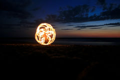 Fire poi on beach in sunset Stock Image