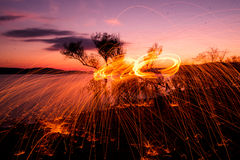 Fire Poi at sunset on the lake Royalty Free Stock Photo