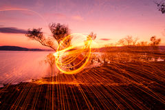 Fire Poi at sunset on the lake Royalty Free Stock Images