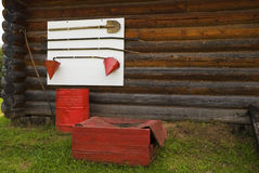 The fire-prevention equipment. On a wall of the wooden rural house. Nearby costs a flank with water and a box with sand Stock Photos