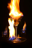 Fire rage and glass. Martini glass inside the fire rage Royalty Free Stock Photography