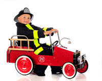 Fire-Ready. An adorable preschool fireman dressed and ready for a fire in his truck.  Isolated on white Royalty Free Stock Images