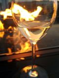 Fire refection in background glass of wine by fireside. Drinking a glass of wine by the fire with the light of the fire burning in the background, reflecting royalty free stock images