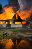 Fire Reflection. The blaze of a burning house is reflected in a pool of runoff from fire hoses Stock Photography