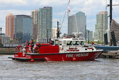 Fire Rescue Boat. Red fire rescue boat parking in the North Cove Marina At Battery Park in Manhattan, NY ,in the background office and residential buildings Royalty Free Stock Image