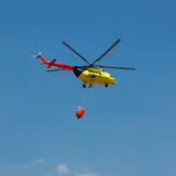 Fire rescue helicopter with water bucket - Square. Crop All copyrighted elements removed royalty free stock photos