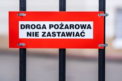 Fire road, keep clear text in Polish on the sign mounted to the fence, white and red plate, black letters stock photo