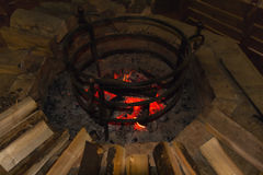Fire in a round hearth and wood Royalty Free Stock Image