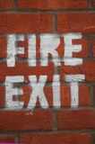Fire Safety. Image of a brick wall with a legally required fire safety exit sign, conceptual corporate health and safety royalty free stock photos