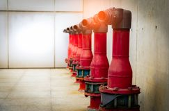 Fire safety pump on cement floor of concrete building. Deluge system of firefighting system. Plumbing fire protection. Red fire. Pump in front of concrete wall royalty free stock image