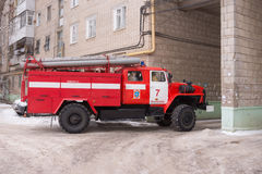 Fire service car leaves from the yard of a multistory building after the call Stock Image