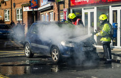 Fire Service put out a car fire. Fire Service crew dowse the flames of a car fire Stock Photos