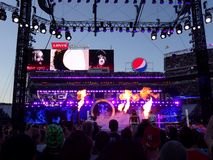 Fire shoots into the air as WWE Wrestler the Undertaker enters arena heading towards the ring with Bray Wyatt standing in that stock photography