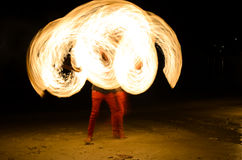 Fire show on the beach. Little boy spinning fire rod show on the beach stock image