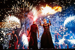 Fire show at night. Young men stands in front of Royalty Free Stock Images