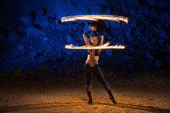 Fire show performance. In the desert near the rock illuminated with blue. Motion blurred stock photography