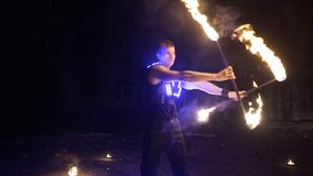 Fire show performance. Handsome male fire performer twirling and tossing up fire baton staff ignited from both sides. stock video footage