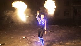 Fire show performance. Handsome male fire juggler performing contact manipulation with fire baton with several wicks stock video footage