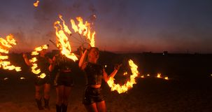 Fire show three women in their hands twist burning spears and fans in the sand with a man with two flamethrowers in slow stock video