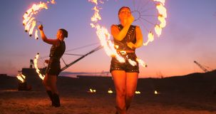 Fire show three women in their hands twist burning spears and fans in the sand with a man with two flamethrowers in slow. Motion stock footage