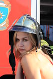 Fire in a skirt. Blond girl in a helmet and a fire truck Stock Photo