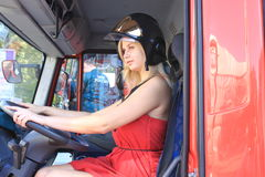 Fire in a skirt. Blond girl in a helmet and a fire truck Stock Photography