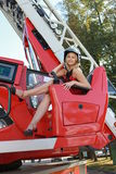 Fire in a skirt. Blond girl in a helmet and a fire truck Royalty Free Stock Image