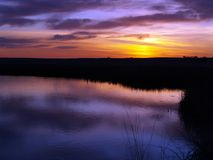 Fire in the Sky. This image of the sunrise with the marsh and pond was taken in west-central Montana Stock Image