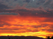 Fire in the sky over the city and mountains - unretouched zoomed Stock Photos