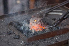 Fire, smoke and blacksmith tools Royalty Free Stock Photo