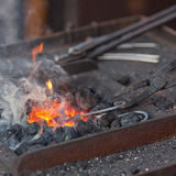 Fire, smoke and blacksmith tools Stock Images
