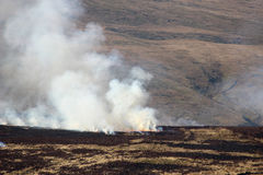 Fire and smoke on burning moorland vegetation. Moorland fire burning on a hillside near Garsdale in North Yorkshire, England Stock Image