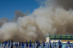 Fire with smoke clouds on the beach with blue umbrellas and sun loungers in Ostia, Italy.  Royalty Free Stock Photography