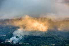 Smoke & clouds lit by golden sunlight on forested slope royalty free stock photography
