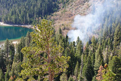 Fire And Smoke In The Forest. Dense smoke rising from the pine forest where a fire has started surrounded by steep hillsides and an emerald green colored lake Royalty Free Stock Photography
