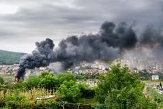 Fire and smoke over the city. Black smoke over the city, coming from burning rubber tires in a warehouse. A big cloud of smoke is rising from the red hot fire Stock Photo
