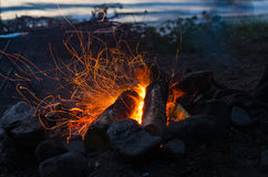 Fire, sparks fire at night. Nochnoy bonfire on the shore of the lake, flying sparks of fire Royalty Free Stock Photography