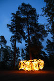 Fire spinning in forest at night Stock Photo