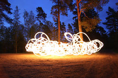 Fire spinning at night in forest Stock Image