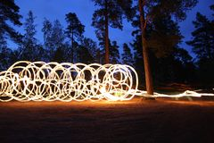 Fire spinning at night in forest Stock Photo