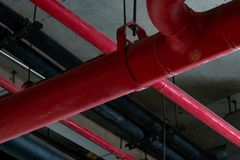 Fire sprinkler system with red pipes hanging from ceiling inside building. Fire Suppression. Fire protection and detector. stock photography