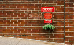 Fire standpipe on a brick wall Stock Photo